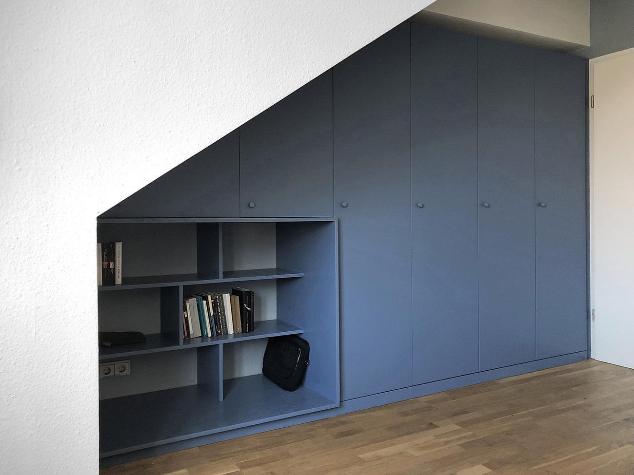 Ein blauer Einbauschrank unter einer Dachschräge