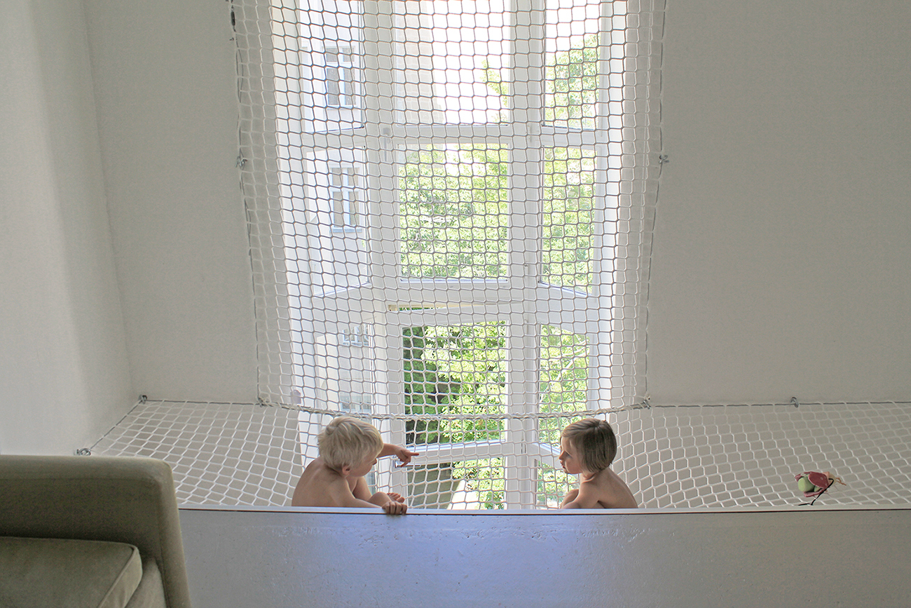 Ein Netz, das als Absturzsicherung eingebaut wurde, indem zwei Kinder sitzen.