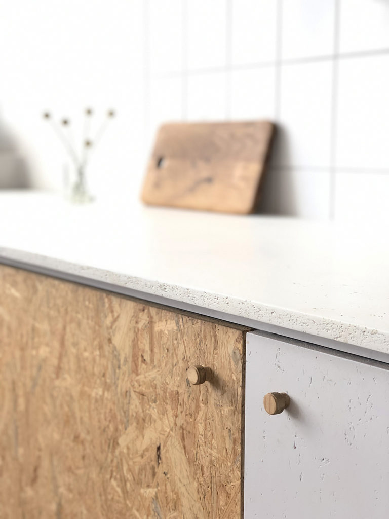 Detailaufnahme der Küchenfronten aus gestrichenen und rohen Holzoberflächen