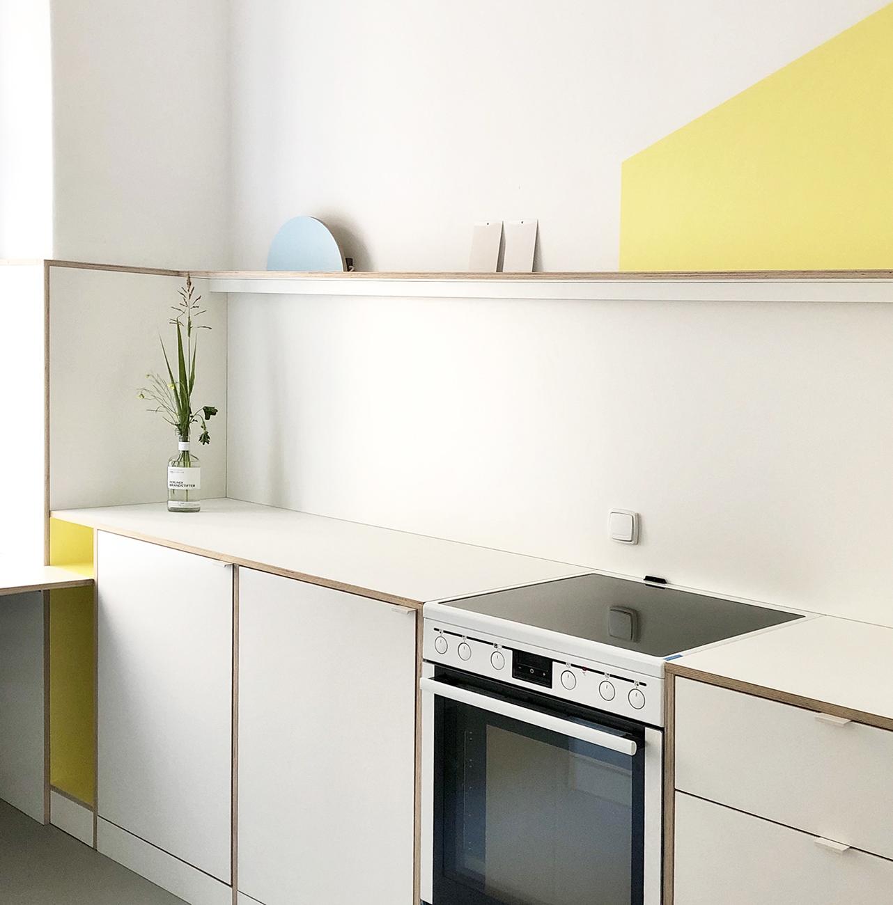 Ein Küchen Design aus weißen Multiplex-Platten mit Holzkanten und farbigen Akzenten in gelb und blau.