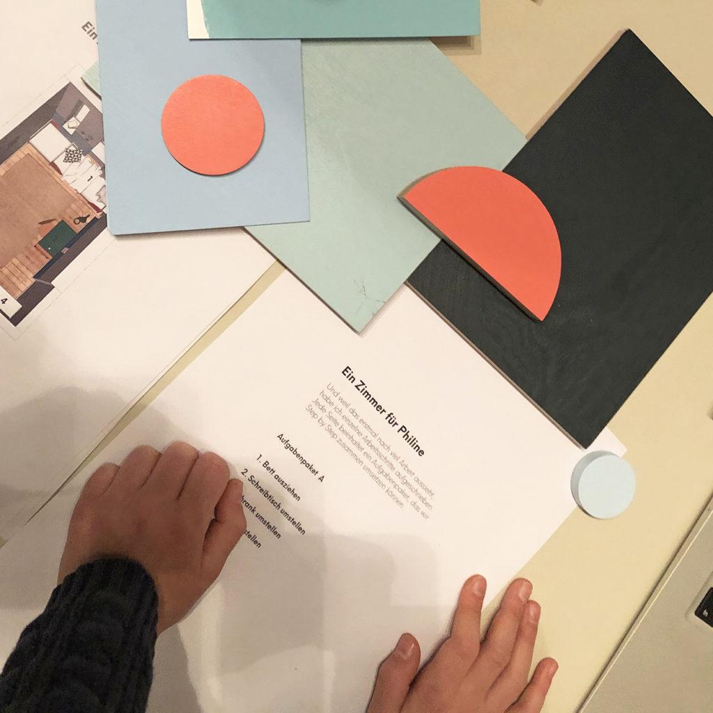 Eine Aufgabe aus dem Workshop ist zu sehen zusammen mit Farb- und Materialmustern.