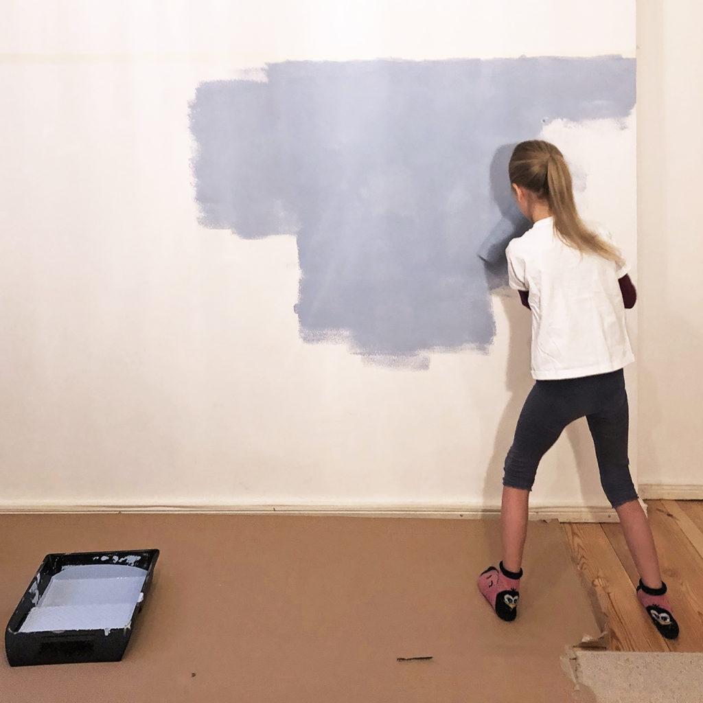 Ein Kind setzt die Ergebnisse aus dem Workshop um und streicht mit blauer Farbe eine Wand.