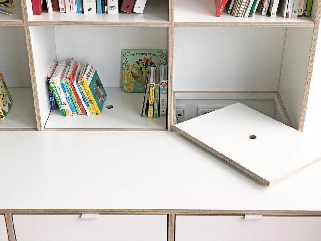 Detailbild des Regals mit Kindertisch aus weißen Multiplex-Platten, auf dem man die Klappen sieht, die von oben befüllt werden können.