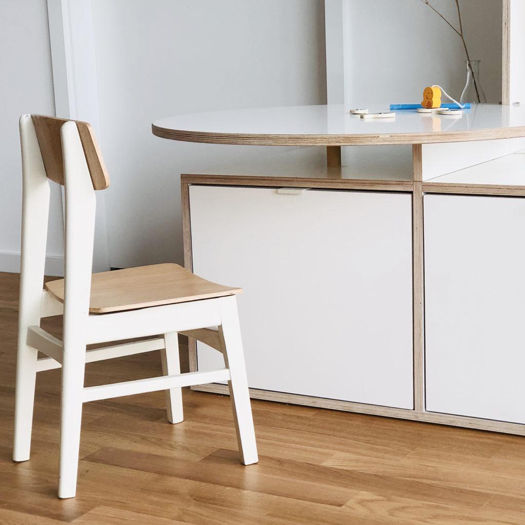 Detailbild von dem Regal auf dem man den Kindertisch mit einem kleinen Kinderstuhl sieht.