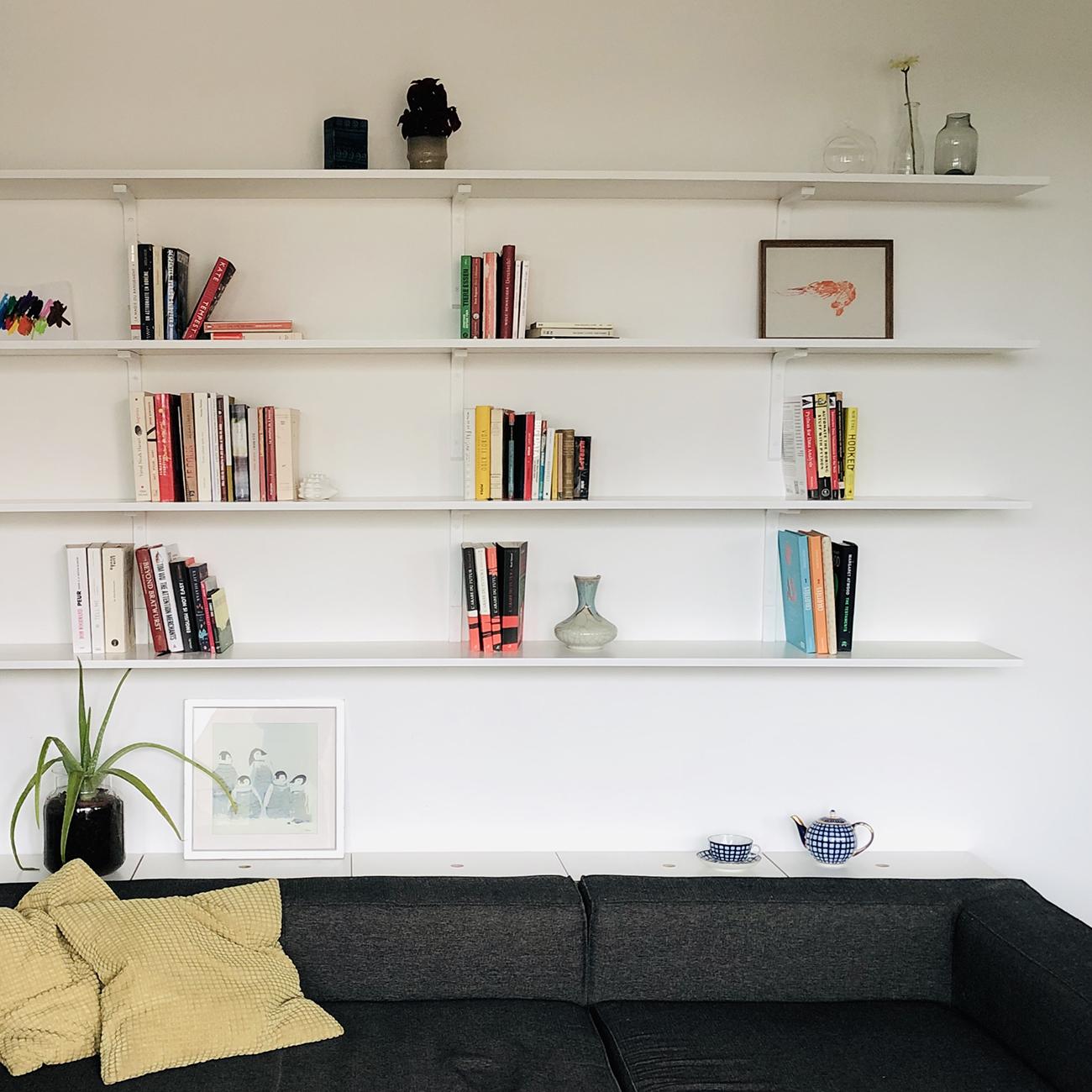 Ein Regal über einem Sofa bestehend aus Multiplex Platten, die über Konsolen an der Wand befestigt sind.