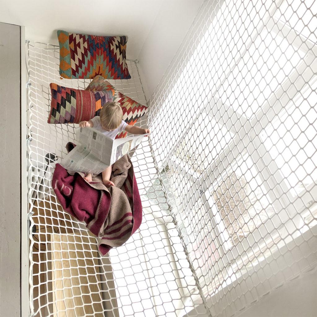 Ein Kind sitzt in einem Netz, das als Absturzsicherung für eine Hochebene dient.