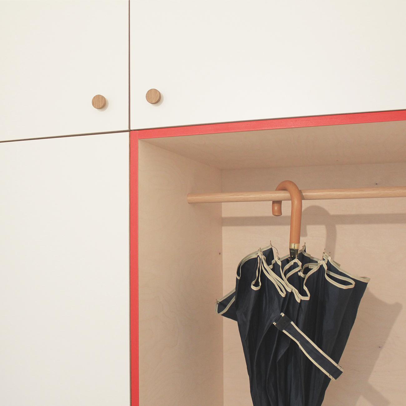 Detailaufnahme einer Garderobe mit pinken Kanten, Schubladen, Kleiderstange und Oberschränken.