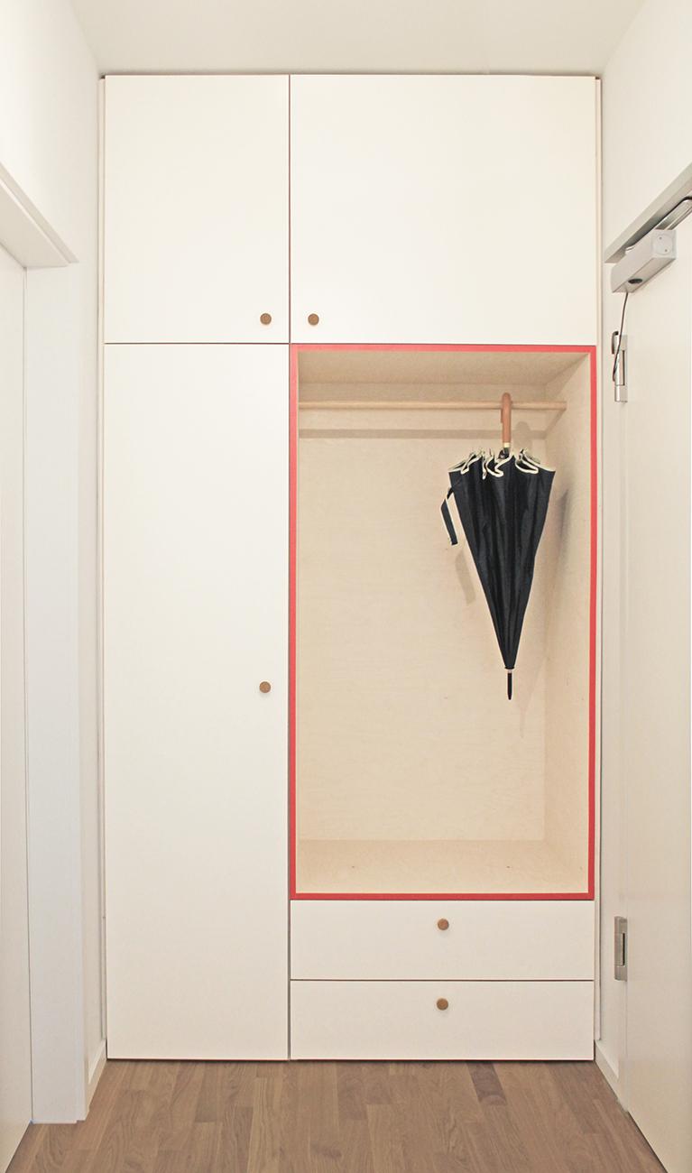 Eine weiße Garderobe mit pinken Kanten, die in eine Nische im Flur eingebaut ist mit Schubladen, Kleiderstange und Oberschränken.