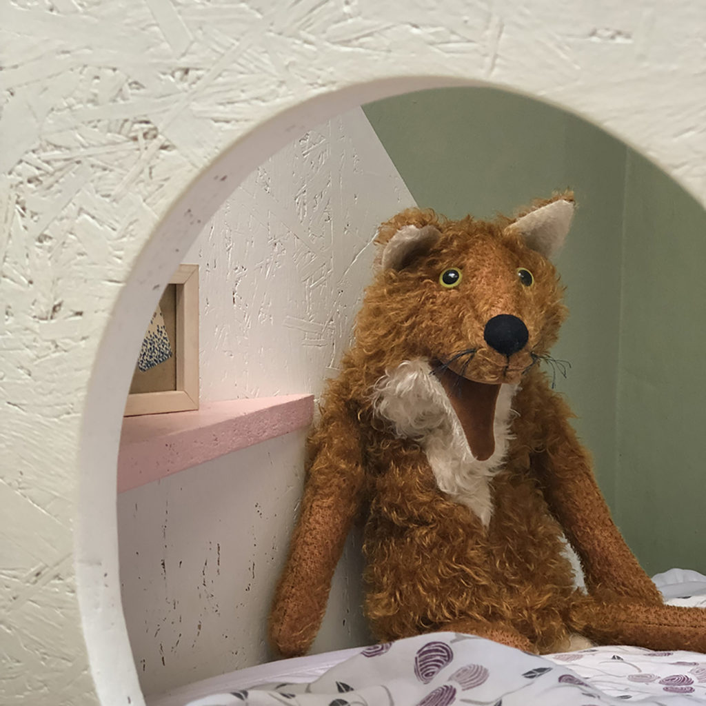 Im Kinderzimmer guckt ein Stofftier durch das rundes Loch eines Kinder Betts.