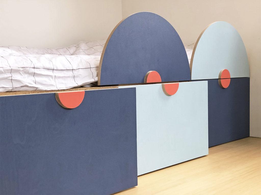 Ein farbiges Kinderbett mit 2 Halbkreisen als Absturzsicherung und 3 Bettkästen zur Aufbewahrung von Kleidern.
