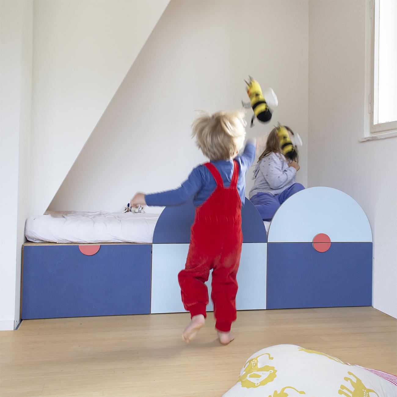 zweifarbiges Kinderbett mit Halbkreisen aus Holz als Absturzsicherung unddrei Schubladen unter dem Bett.