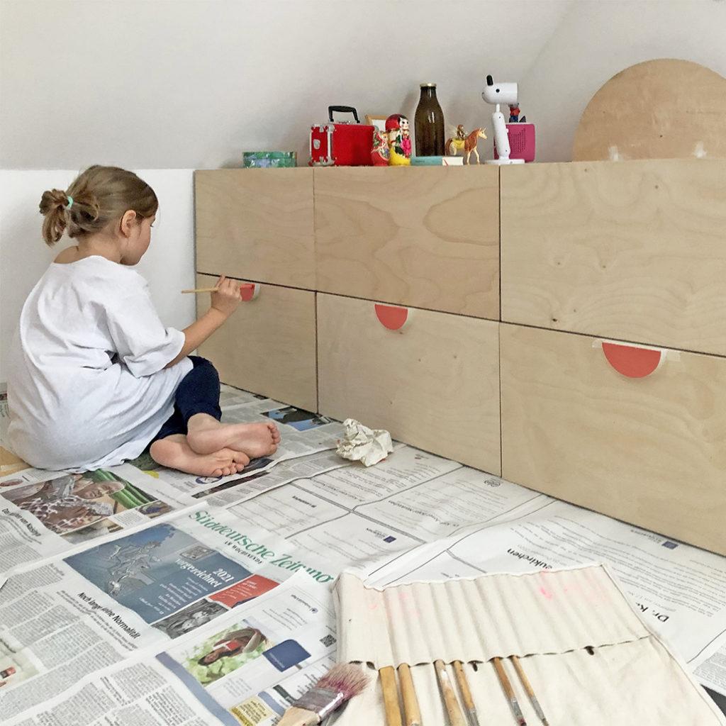 Ein Kind, welches die Schubladengriffe des eigenen Kinderbetts streicht.
