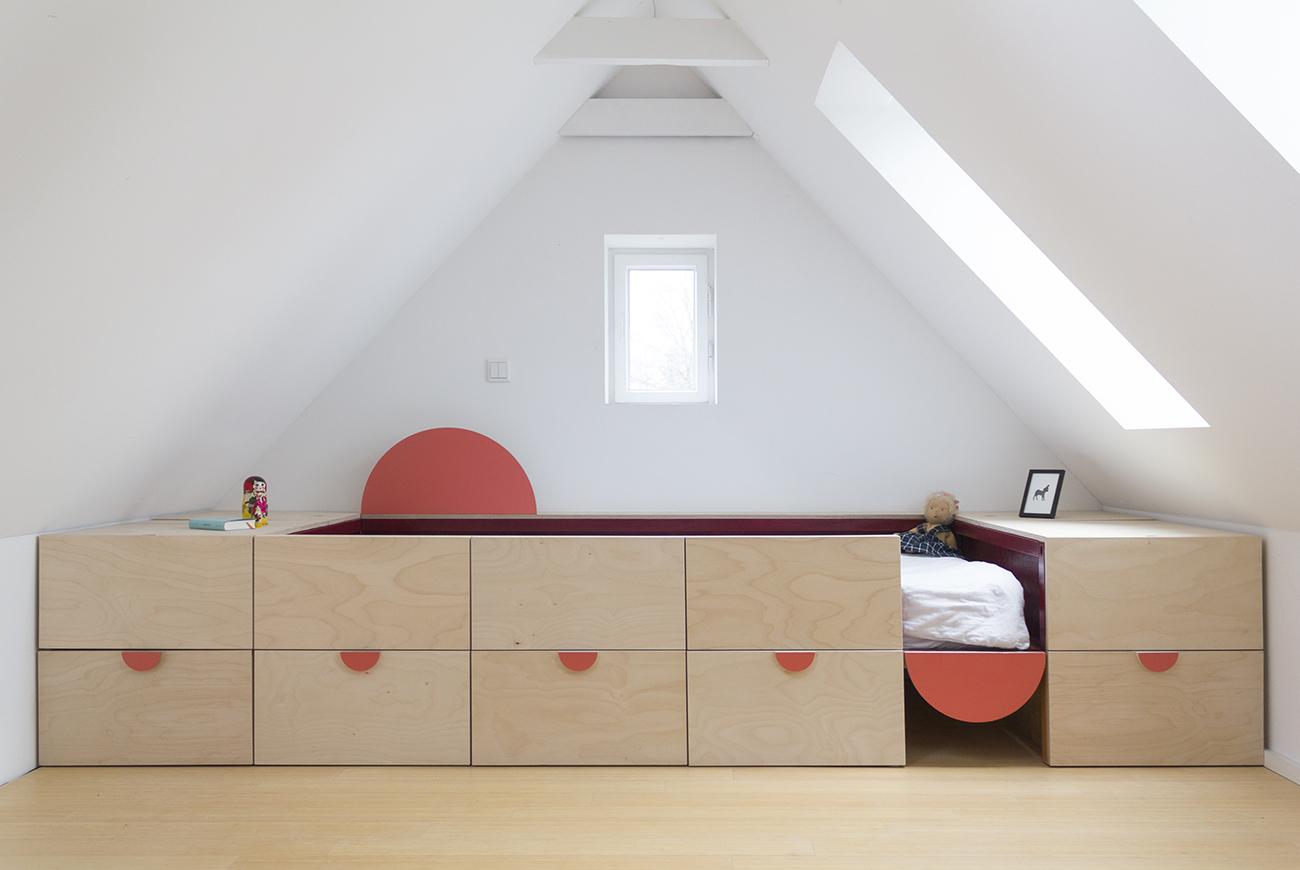 Ein Bett für ein Kinderzimmer aus Multiplex Birke natur mit Schubladen und dekorativen Halbkreisen, die bunt gestrichen sind.